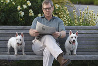 Man sitting with dogs on park bench