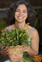 Hispanic woman gardening 11029016807| 写真素材・ストックフォト・画像・イラスト素材|アマナイメージズ