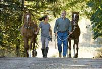 Couple walking horses on country lane