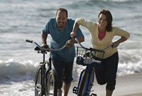 Couple pushing bicycles on beach
