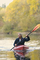 Woman paddling kayak on river in autumn