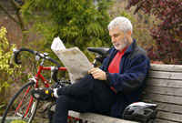 Man with bicycle reading newspaper in park