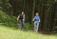 Couple riding bicycles in woods