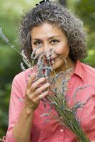 Asian woman smelling lavender 11029016900| 写真素材・ストックフォト・画像・イラスト素材|アマナイメージズ