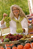 Woman holding grapes at outdoor market