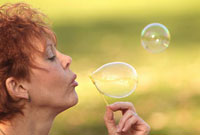 Woman blowing bubbles in park