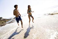 Multi-ethnic couple running on beach