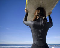 Female surfer carrying surfboard