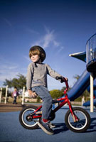 Young boy riding bicycle in playground