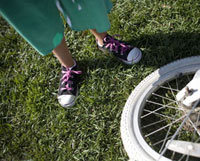 Childis feet next to bicycle wheel