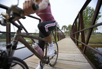 Woman riding bicycle over footbridge
