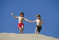 Boys holding hands and running down sand dune