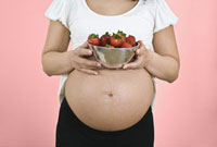 Pregnant woman holding bowl of strawberries