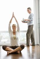 Man holding magazine and woman doing yoga