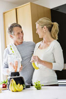 Couple preparing health shake in kitchen,