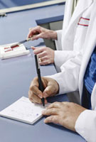 Close up of pharmacist writing on prescription pad