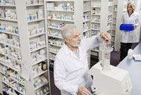 Pharmacist pouring pills into counting machine