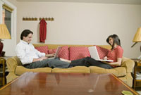 Couple with laptops laying on sofa in living room