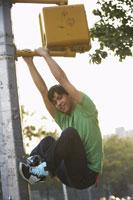 Teenaged Boy Climbing on Traffic Light 11030020964| 写真素材・ストックフォト・画像・イラスト素材|アマナイメージズ
