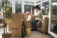 Woman Packing Boxes in Sunroom 11030022980| 写真素材・ストックフォト・画像・イラスト素材|アマナイメージズ