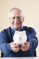 Portrait of Senior Man Holding a Piggy Bank