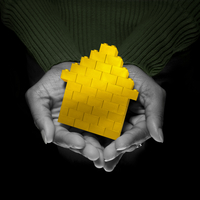Close-up of Woman's Hands holding Yellow Brick House, Studio