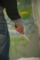 Close-up of Young Man Holding Knife with Grafitti in Backgro 11030036500| 写真素材・ストックフォト・画像・イラスト素材|アマナイメージズ