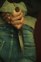 Close-up of Young Man holding Knife Behind Back