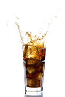 Ice Splashing on a Glass of a Cola Drink Against a White Bac