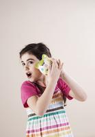 Portrait of Girl Shaking Piggy Bank and Listening in Studio 11030036803| 写真素材・ストックフォト・画像・イラスト素材|アマナイメージズ