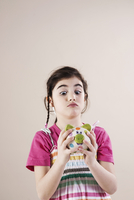Portrait of Girl Looking Cross Eyed at Piggy Bank in Studio