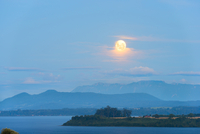 Moon rising between the clouds over Lake Llanquihue, X Regio