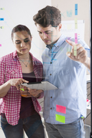 Young Man and Young Woman Working in an Office, Looking Thro
