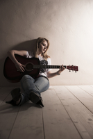 Young Woman Sitting on the Floor Playing Guitar in Studio
