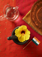 Hibiscus Flower in Mortar with Pestle, Jug of Water and Indian flag on Red Background