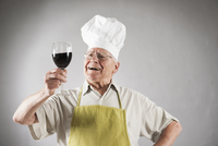 Senior Man with Red Wine wearing Apron and Chef's Hat, Studio Shot