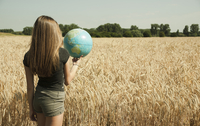 Backview of teenaged girl standing in wheat field, holding globe, Germany