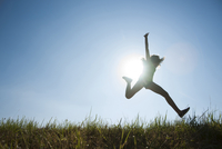 Silhouette of teenaged girl jumping in air across field, Germany