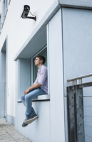 Young man sitting on ledge outdoors, Germany