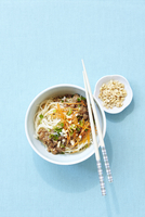 Overhead View of Noodles with Pork, Peanuts, and Shredded Carrot in Bowl with Chopsticks