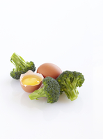 Raw Broccoli and Cracked Egg, White Background, Studio Shot