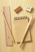 notebook, ruler and pencils on wooden background, studio shot