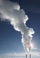 Industrial smoke stacks with steam billowing into blue sky, Toronto, Ontario, Canada