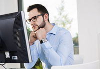 Close-up of young businessman looking at computer monitor in office, Germany