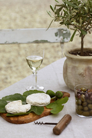 Cheese rounds of Tome de Provence, goat cheese, bowl of olives and aperitif drink, on table in garden, Provence, France