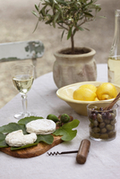 Cheese rounds of Tome de Provence, goat cheese, bowls of lemons and olives and aperitif drink on table, Provence, France