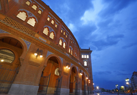 Exterior of the Las Ventas bullring at Plaza de Toros illuminated at dusk under stormy skies, Madrid, Spain