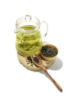 Green Tea Steeping in Tea Pot with Dried Tea Leaves in Wooden Bowl on White Background
