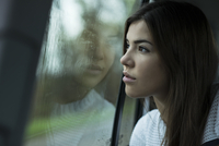 Portrait of young woman sitting inside car and looking out of window and day dreaming on overcast day, Germany