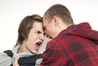 Close-up of two teenage boys fighting and screaming at each other, studio shot on white background